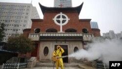 一名工人在武漢漢口教堂救世堂前為防疫新冠病毒噴灑消毒藥水。 (2020年3月6日)