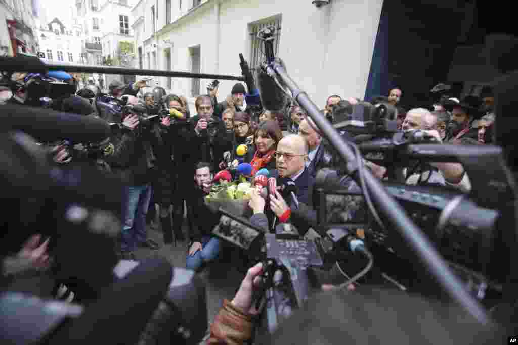 French Interior Minister Bernard Cazeneuve and Paris Mayor Anne Hidalgo address reporters after visiting the Jewish school of the Rue Pavee, in the heart of the Paris Jewish quarter, Jan. 12, 2015.