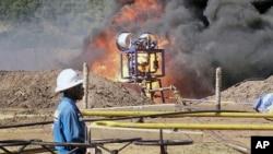 FILE- An oil well undergoes testing in the Lake Albertine region of western Uganda.
