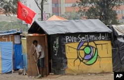 "In this Tuesday, Dec. 12, 2017 photo, bricklayer Luciano Oliveira sweeps outside his shack in the squatter community coined ""Povo Sem Medo,"" or Fearless People, in Sao Bernardo do Campo,"