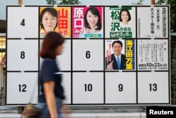 A woman walks past candidates' posters for the October 22 lower house election in Tokyo, Japan, Oct. 10, 2017.