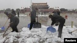 Солдаты военизированной милиции убирают снег на площади Тяньаньмэнь, Пекин. Китай, 4 ноября 2012 года