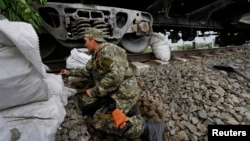 5月12日,一名親俄反政府武裝成員以火車車廂為掩護,守衛在烏克蘭東部城市斯拉維揚斯克的前沿陣地。