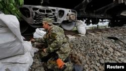 一名亲俄反政府武装成员以火车车厢为掩护,守卫在乌克兰东部城市斯拉维扬斯克的前沿阵地。(2014年5月12日)