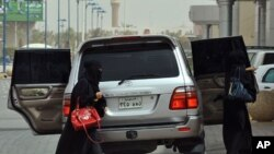 Saudi women get out of the backseats of a car in Riyadh on June 17, 2011