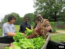 Bladensburg, Maryland Mayor Walter James gets his pick of produce from the Philip Sidibe, Adam Sidibe and Wudood Omran. (Rosanne Skirble/VOA)