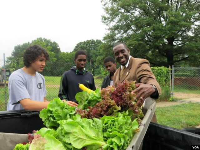 Bladensburg, Maryland Mayor Walter James gets his pick of produce from the Philip Sidibe, Adam Sidibe and Wudood Omran. (Rosanne Skirble/VOA)