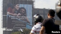 FILE - Motorists ride past a billboard displaying Facebook's Free Basics initiative in Mumbai, India.