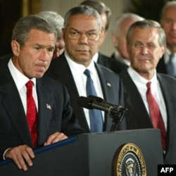 President Bush with Secretary of State Colin Powell and Secretary of Defense Donald Rumsfeld. The president spoke to reporters before signing a congressional resolution for the use of force against Iraq.