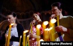 Perempuan menyalakan lilin selama kebaktian Paskah Ortodoks di Biara St. Sava di Beograd 5 Mei 2013. (Photo: REUTERS/Marko Djurica)