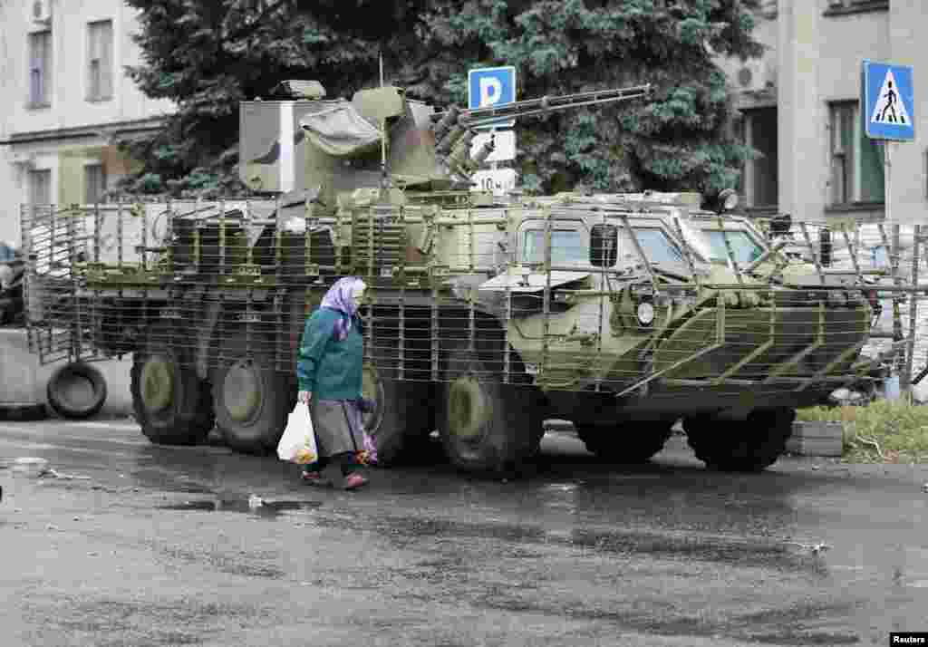 A local resident walks past a Ukrainian armored vehicle in the eastern Ukrainian city of Kramatorsk, July 7, 2014.