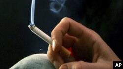 FILE - A woman smokes a cigarette.
