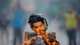 Anti-government protesters burn an effigy depicting Venezuela's President Nicolas Maduro in Caracas April 20, 2014.