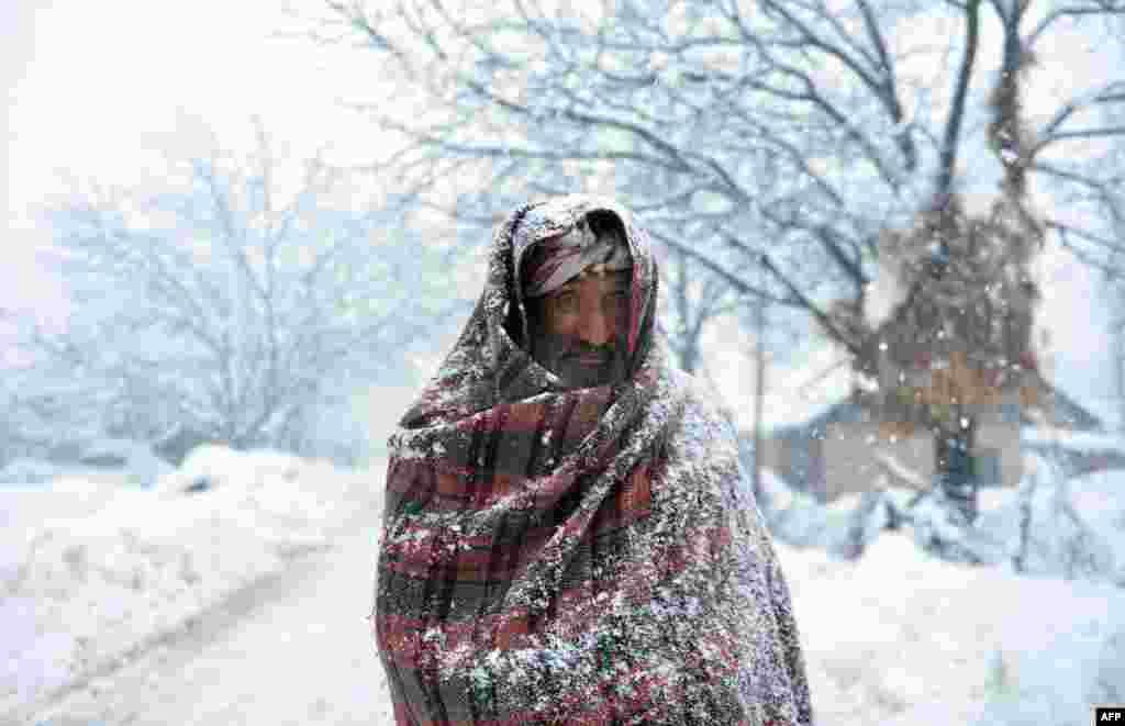 អ្នកភូមិជនជាតិ Kashmiri ចំណាស់ម្នាក់ដើរកាត់ព្រិលក្នុងទីក្រុង Gund ប្រហែល៧០ គ.ម. ភាគឦសានទីក្រុង Srinagar ប្រទេសឥណ្ឌា។