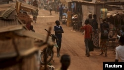 FILE - A boy walks in a camp sheltering internally displaced people next to the M'Poko international airport in Bangui, Central African Republic, Feb. 13, 2016.
