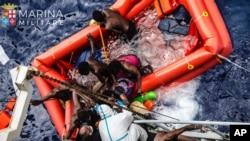 Đội cứu hộ giúp các di dân lên tàu Vega của Hải quân Italia sau khi tàu của những di dân này bị chìm ngoài khơi Libya, Địa Trung Hải, 27/5/2016.