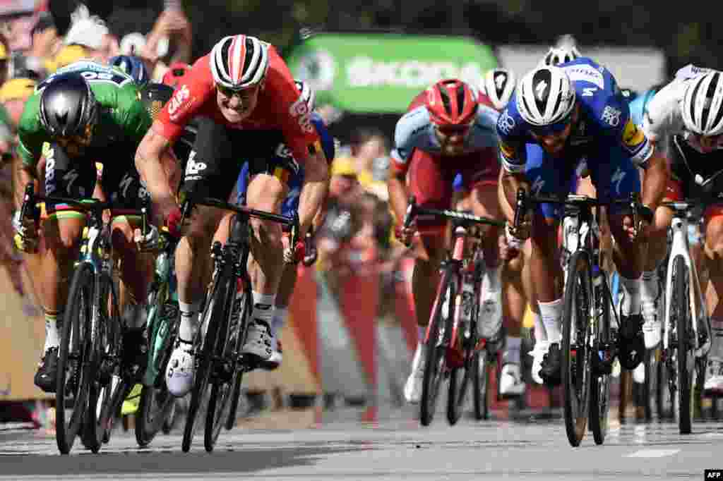 Colombia's Fernando Gaviria (C) sprints in the last meters to cross the finish line ahead of Slovakia's Peter Sagan (L) and Germany's Andre Greipel (2ndL) to win the fourth stage of the 105th edition of the Tour de France cycling race between La Baule and Sarzeau, western France.