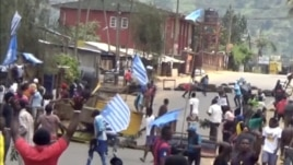 A still image taken from a video shot Oct. 1, 2017, shows protesters waving Ambazonian flags in front of road block in the English-speaking city of Bamenda, Cameroon.
