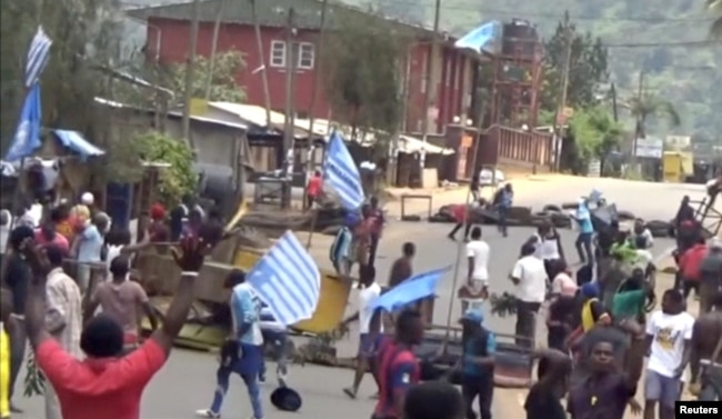 FILE - A still image taken from a video shot Oct. 1, 2017, shows protesters waving Ambazonian flags in front of road block in the English-speaking city of Bamenda, Cameroon.