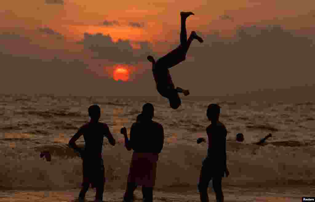 Một cậu bé chơi trò nhào lộn trên bãi biển lúc hoàng hôn, ở Colombo, Sri Lanka