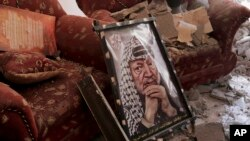 FILE - A poster of Palestinian leader Yasser Arafat is seen on the rubble of a destroyed house in the Bureij refugee camp in the central Gaza Strip, Aug. 1, 2014.
