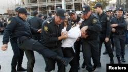 Polis müxalif nümayiş iştirakçısını döyür. Bakı, 12 oktyabr, 2013.