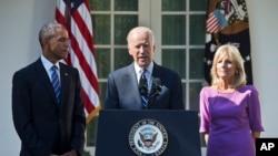 Wakil Presiden AS Joe Biden, didampingi istrinya Jill dan Presiden Barack Obama, mengumumkan bahwa ia tidak akan maju dalam nominasi pemilihan presiden (21/10). (AP/Jacquelyn Martin)