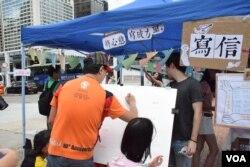 支持者在集會攤位寫信給在囚抗爭者。(美國之音湯惠芸)