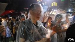 參加六四燭光晚會的人士身穿雨衣,並小心保護手中的燭光免被雨水淋息