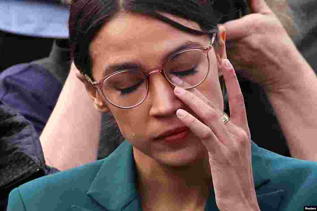U.S. Representative Alexandria Ocasio-Cortez (D-NY) wipes tears as Representative Ilhan Omar (D-MN) talks about her own experience as a refugee during a news conference to call on Congress to cut funding for ICE (Immigration and Customs Enforcement), at the U.S. Capitol in Washington, D.C.