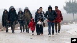Un grupo de migrantes caminan cerca de la frontera entre Serbia y Croacia en medio del frío.