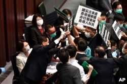 Hong Kong pro-democracy lawmakers holding up placards are blocked by security as they protest during a House Committee meeting, chaired by pro-Beijing lawmaker Starry Lee (L-in white jacket)