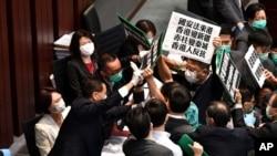 香港立法会泛民主派议员在内务委员会的一个会议期间举牌抗议中国人大制定香港国安法,他们被保安阻拦。(2020年5月22日)