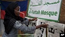 Darlene Derosier menempelkan petunjuk cara membersihkan diri, atau berwudhu, di Masjid Al-Fattah di Gressier, Haiti. (AP)