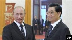 ທ່ານ Vladimir Putin ນາຍົກລັດຖະມົນຕີຣັດເຊຍ ຈັບມືກັບທ່ານ ຫູຈິນເຖົາ ປະທານປະເທດຈີນ. ວັນທີ 12 ຕຸລາ 2011.