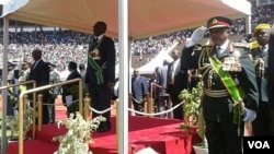 President Mugabe inspecting a guard of honour in Harare Monday at the National Sports Center.