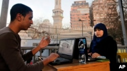 FILE - Egyptians log on to the Internet at a community center in front of a mosque in Cairo, Egypt, Saturday, Feb. 9, 2013.