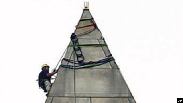 Dave Megerle attaches ropes to the top of the Washington Monument, from which four people will rappel down the sides to survey the extent of damage sustained to the monument from the August 23 earthquake, on the National Mall, in Washington, September 27,