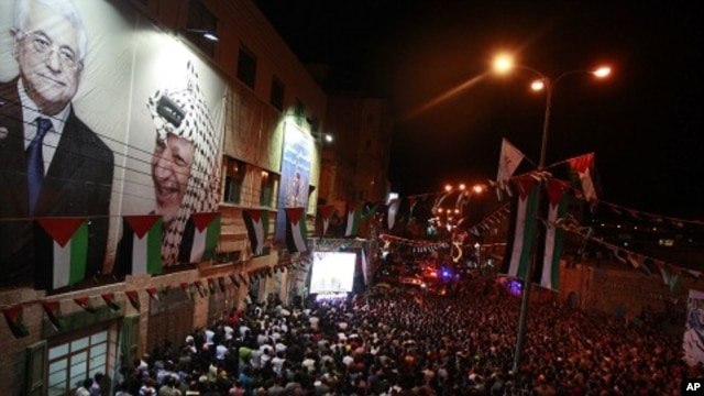 Palestinians watch their President Mahmoud Abbas on TV as he delivers his speech at the General Assembly of the United Nations, in the West Bank city of Hebron, September 23, 2011.
