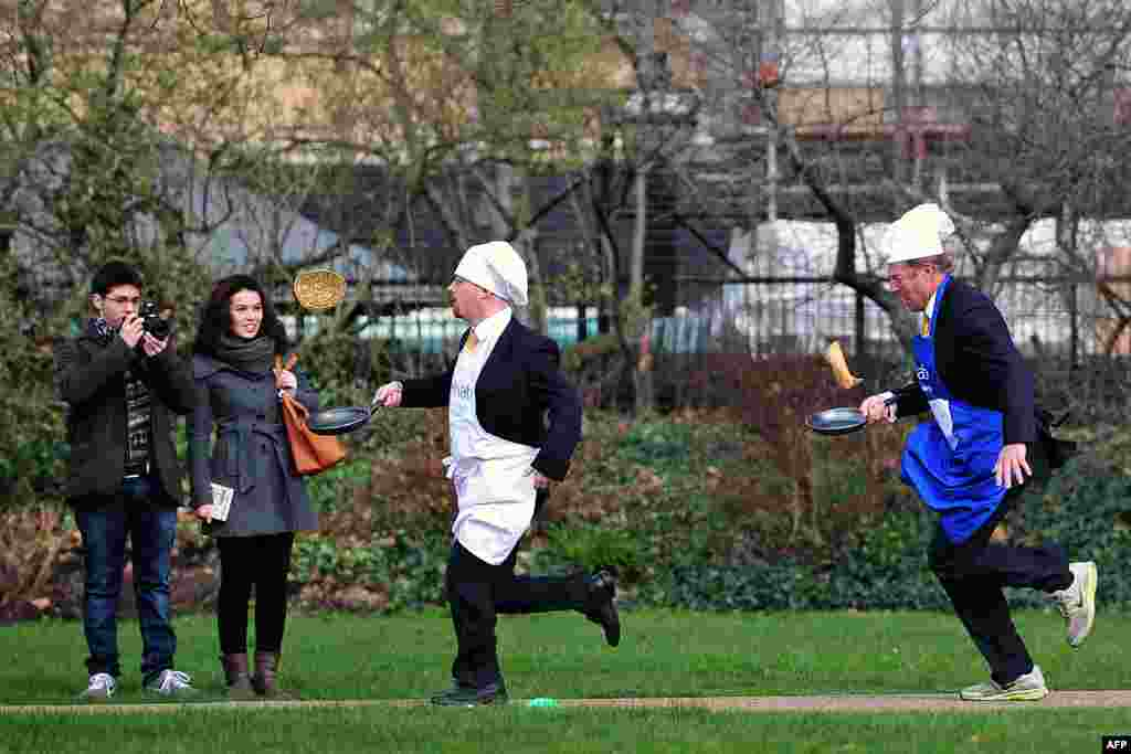 British parliamentarians Lord St John of Bletso (R) and Julian Huppert MP (2nd R) take part in the annual parliamentary pancake race on Shrove in central London.