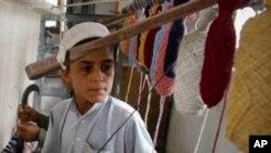 Criança paquistanesa na tecelagem