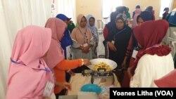 Para perempuan mempraktikkan cara membuat camilan kacang sembunyi dalam kegiatan pelatihan keterampilan di Petobo, Kota Palu, Sulawesi Tengah, Rabu, 18 September 2019. (Foto: Yoanes Litha/VOA)