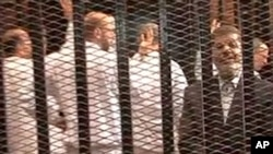 FILE - Image made from video provided by Egypt's Interior Ministry shows ousted President Mohammed Morsi, right, speaking from the defendant's cage as he stands with co-defendants in a makeshift courtroom during a trial hearing in Cairo, Nov. 4, 2013.