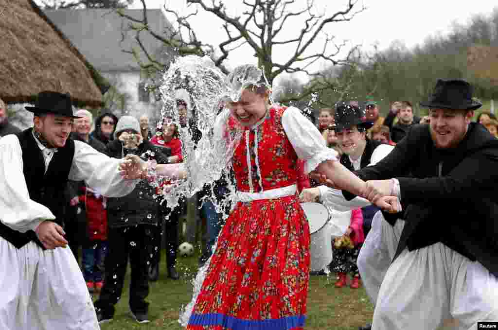 Men throw water on a woman as part of traditional Easter celebrations in Szenna, Hungary.