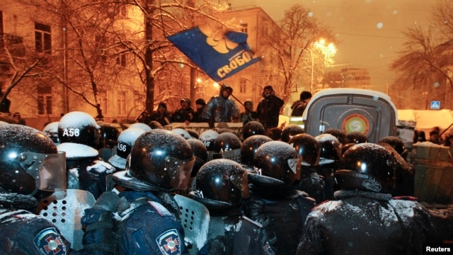 Riot police gather to remove a barricade set up by supporters of EU integration in  Kyiv, Dec. 9, 2013.