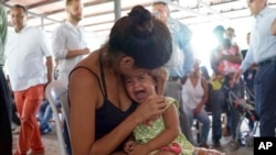 FILE - A Venezuelan woman holds a girl at a health post for migrants in Cucuta, along Colombia's border with Venezuela, July 16, 2018.