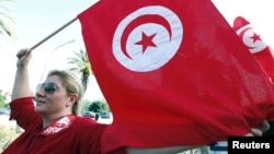 FILE - A woman waves a Tunisia flag during a rally to protest against religious and political violence in Tunis, Oct. 22, 2012.