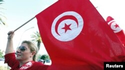 FILE - A woman waves a Tunisia flag in Tunis, Oct. 22, 2012.