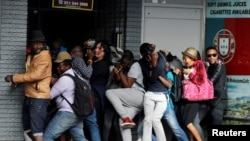 Students demanding free education react as they are fired at by riot police officers during a protest outside the University of the Witwatersrand in Johannesburg in October.