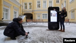 FILE - A woman poses for a photo near the iPhone-shaped monument to Apple co-founder Steve Jobs at the State University of Information Technologies, Mechanics and Optics in St. Petersburg in January 2013.
